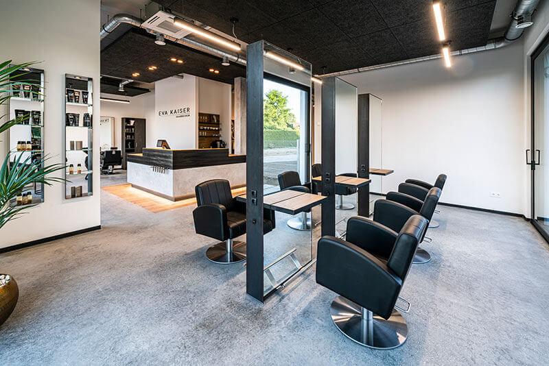 Friseureinrichtung mit Friseurspiegel doppelt mit Ablage als Bedienungsplatz und Friseurstühlen, mit Rezeption im Hintergrund